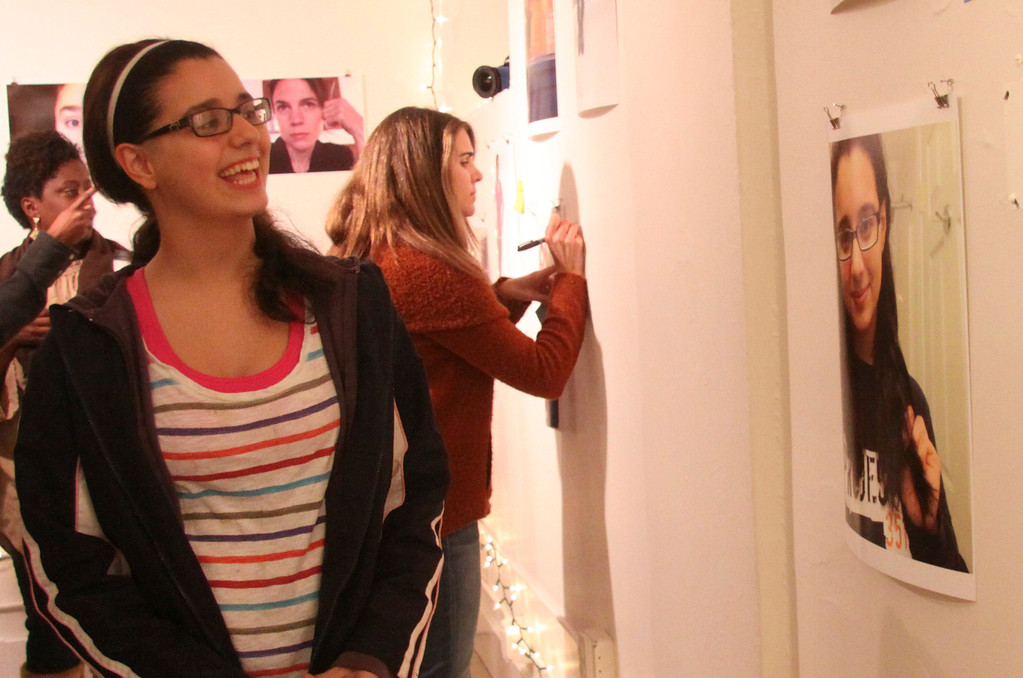 Description of . Yasamin Moeini a smiles as she finds a self portrait of herself during the selfi gallery exhibit held in great barrington on Friday evening . The selfi exhibit was part of the Dove Campaign for Real Beauty. Dove and Monument mountain high school came together with students of the high school to see what insecurities the female students felt and then were asked to take self portraits of themselves and be photographed with their mothers. The gallery visitors were then asked to come visit and write positive comments and stick them on every photo. November 22nd 2013 Holly Pelczynski/Berkshire Eagle Staff