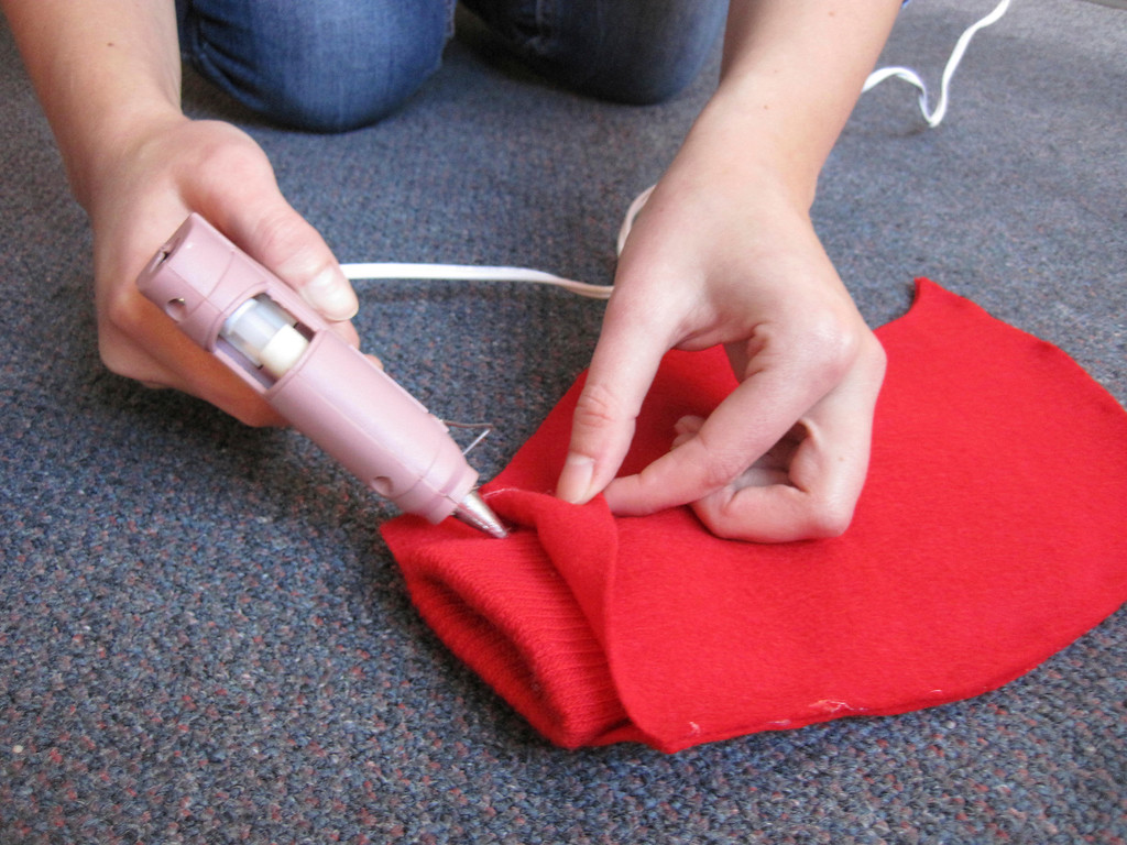 Description of . Eagle online editor Laura Lofgren hot glues hand-traced, hand-cut red felt lobster claw shapes over a red glove to creates a DIY lobster claw, as used in a homemade 'Lobster-in-a-Pot' costume worn by Eagle features editor Lindsey Hollenbaugh. Jenn Smith/Berkshire Eagle Staff Oct. 18, 2013