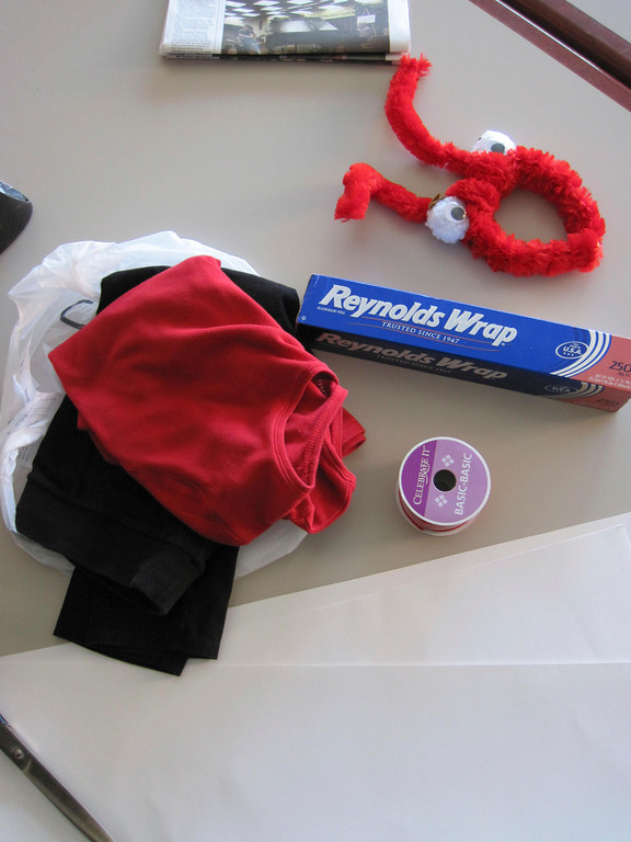 Description of . A red shirt, black pants, posterboard, aluminum foil, red ribbon, pom-poms, stick-on googly eyes and a pipe cleaner-covered headband were crafted together to create a DIY
