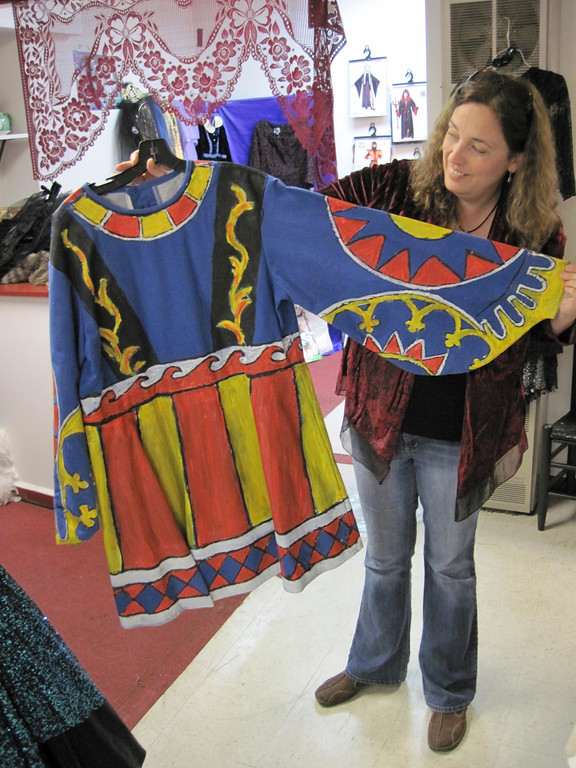 Description of . Berkshire Costume Company owner Kara Demler shows off a vintage plain blue tunic painted with fabric paint to transform it into a royal garment. Jenn Smith/Berkshire Eagle Staff Oct. 18, 2013