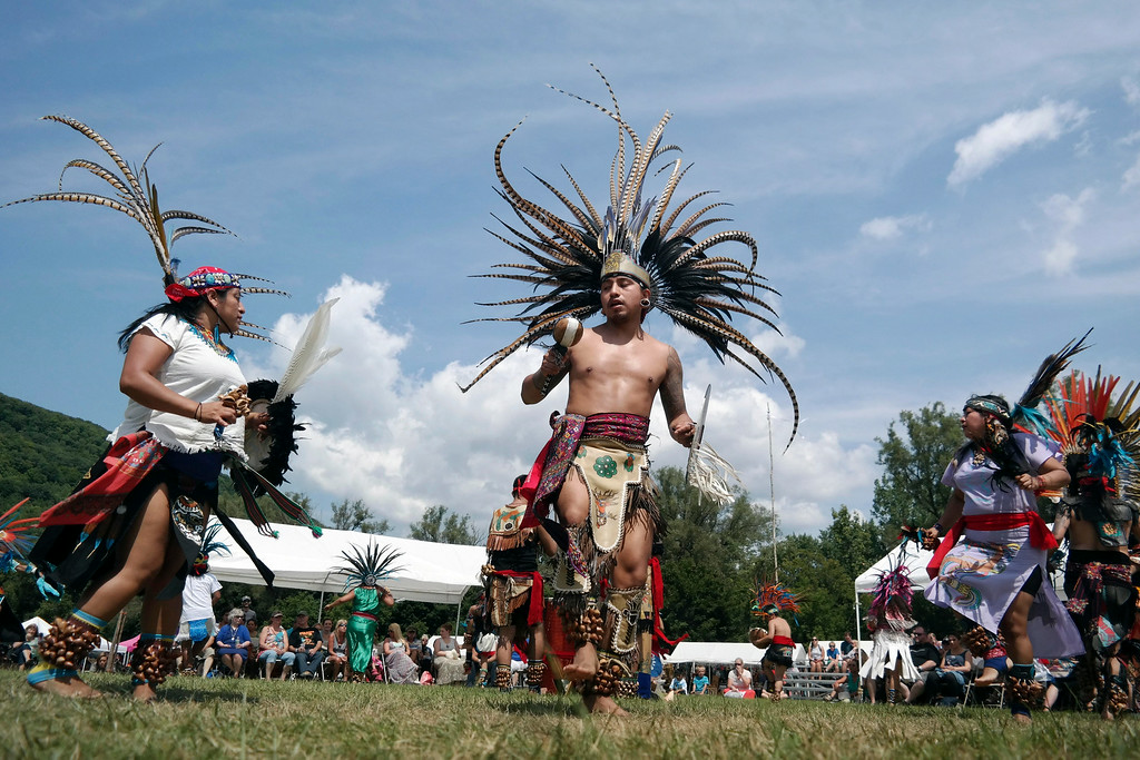 Description of . Kalpulli Atl-Tlachinolli dancers of New York perform a dance celebrating the groth of maize (corn) at the Rock, Rattle and Drum Pow Wow in Adams, Mass., Sunday Aug. 10, 2014.  The event celebrates contemporary and traditional Native American cultures and draws people from the Northeast. (AP Photo / The Berkshire Eagle, Ben Garver)