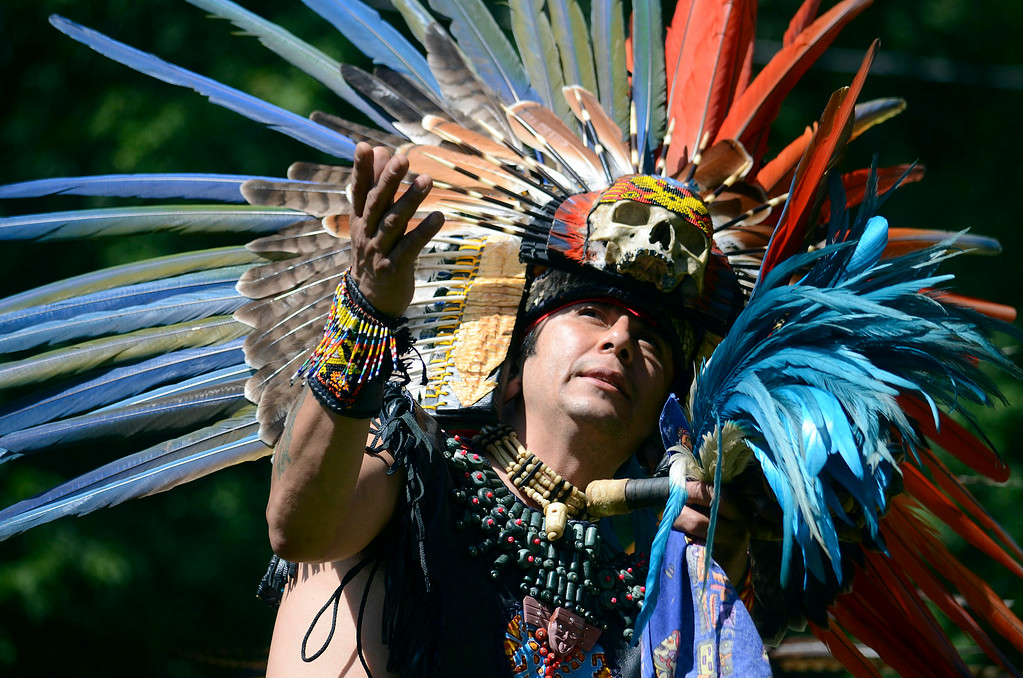 Description of . Gustavo Arias, a dancer from Kalpulli Atl-Tlachinolli from New York, dances in an Aztec tradition at the Rock, Rattle and Drum Pow Wow in Adams, Mass., Sunday Aug. 10. 2014.  The event attracts native American traditions from around the Northeast. (AP Photo / The Berkshire Eagle, Ben Garver)