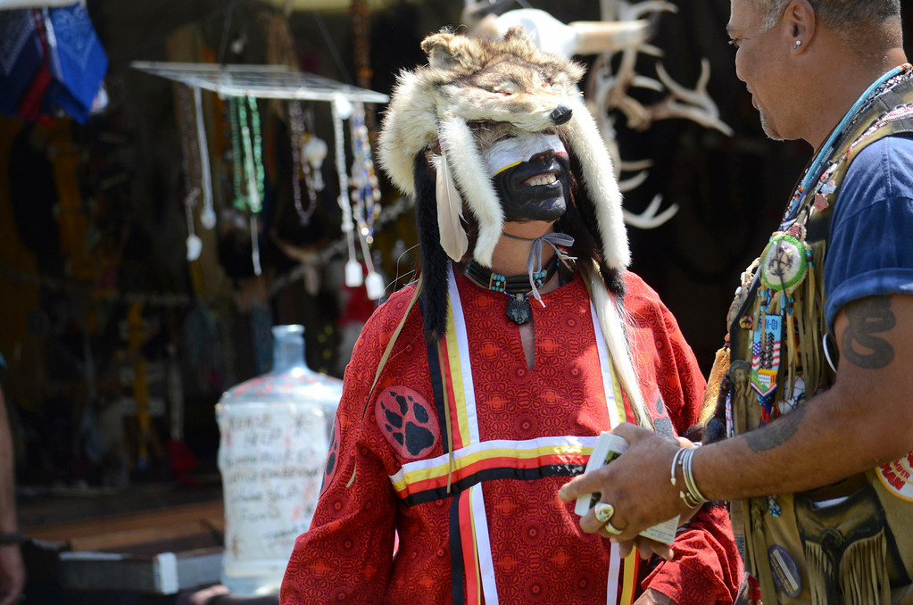 Description of . Harold Shadowwolf (in the traditional regalia of the dog-soldier) catches up with Tony Moonhawk at the Rock, Rattle and Drum Pow Wow in Adams, Mass., Sunday Aug. 10. 2014.  Shadowwolf is a member of the Cheyanne Nation and lives in Biddeford, ME.  (AP Photo / The Berkshire Eagle, Ben Garver)