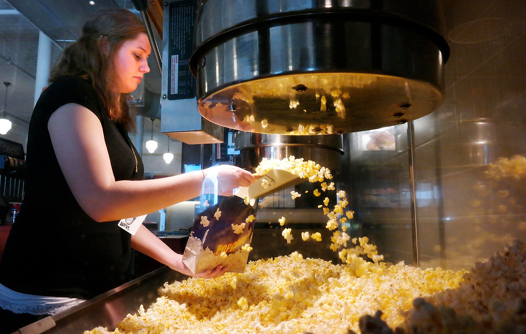 Description of . Brianna Flynn prepares popcorn at the Beacon Cinema. The Beacon Cinema in Pittsfield does not allow outside food, and is implementing a more customer-friendly approach to enforcing the rule. Monday May 12, 2014.  Ben Garver / Berkshire Eagle Staff / photos.berkshireeagle.com