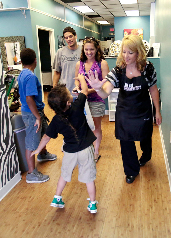 Description of . Kingston DeJesus 5, gives a high five to Bre Calkins after she gave him his first hair cut at Split Ends Hair Salon in Pittsfield. Saturday, August 3, 2013. Stephanie Zollshan/Berkshire Eagle Staff.