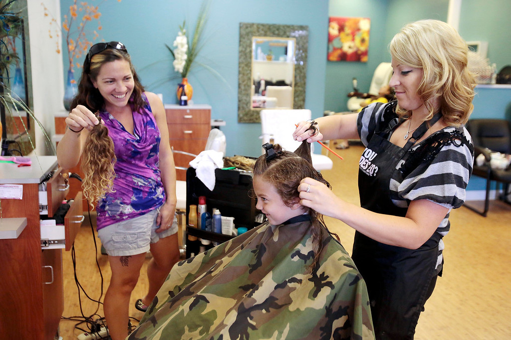 Description of . Sarah DeJesus shows her son Kingston 5, the 15 inches of hair that he will be donating to Wigs for Kids, as he gets his first haircut from Bre Calkins at Split Ends Hair Salon in Pittsfield. Saturday, August 3, 2013. Stephanie Zollshan/Berkshire Eagle Staff.