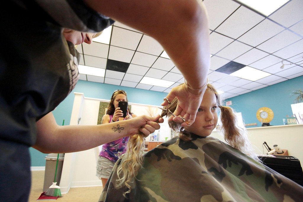 Description of . Sarah DeJesus records video as her son Kingston 5, gets his first haircut from Bre Calkins at Split Ends Hair Salon in Pittsfield. Saturday, August 3, 2013. Stephanie Zollshan/Berkshire Eagle Staff.