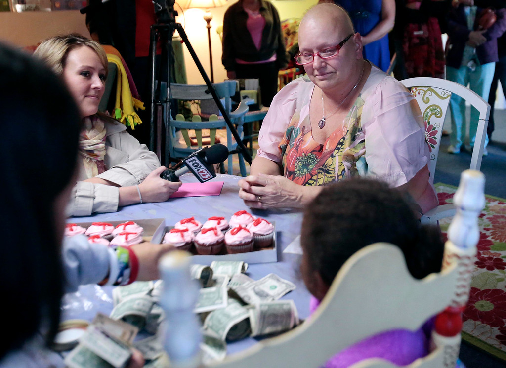Description of . Emma Msibi, 4, gives a jar of money to Sharon Debonis, a cancer victim and recipient of the proceeds from Msibi and her twin sister Eva's lemonade stand at Moments House in Pittsfield. Monday, September 23, 2013. Stephanie Zollshan/Berkshire Eagle Staff.