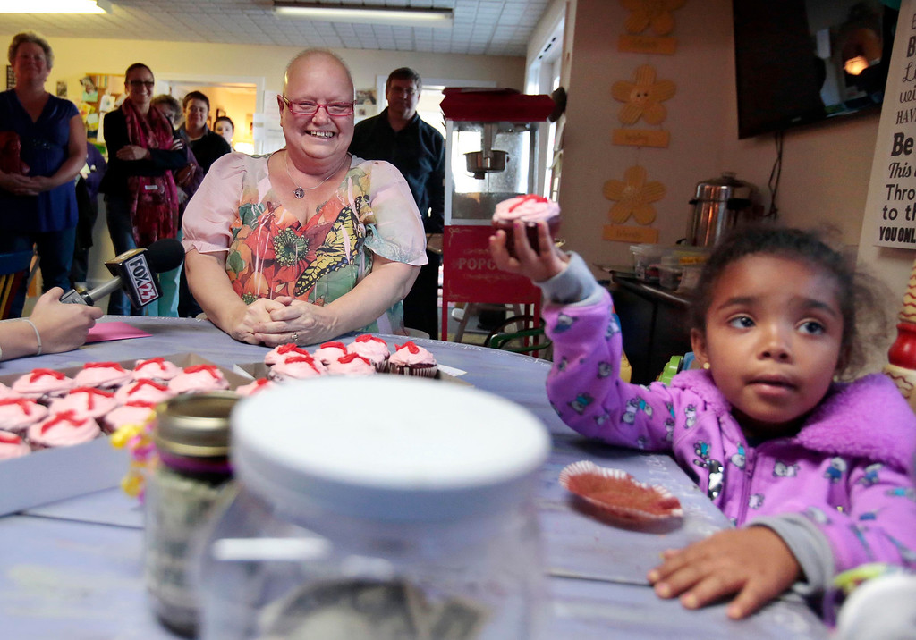 Description of . Emma Msibi, 4, eats a cupcake made for her by Sharon Debonis, a cancer victim and recipient of the proceeds from Msibi and her twin sister Eva's lemonade stand at Moments House in Pittsfield. Monday, September 23, 2013. Stephanie Zollshan/Berkshire Eagle Staff.