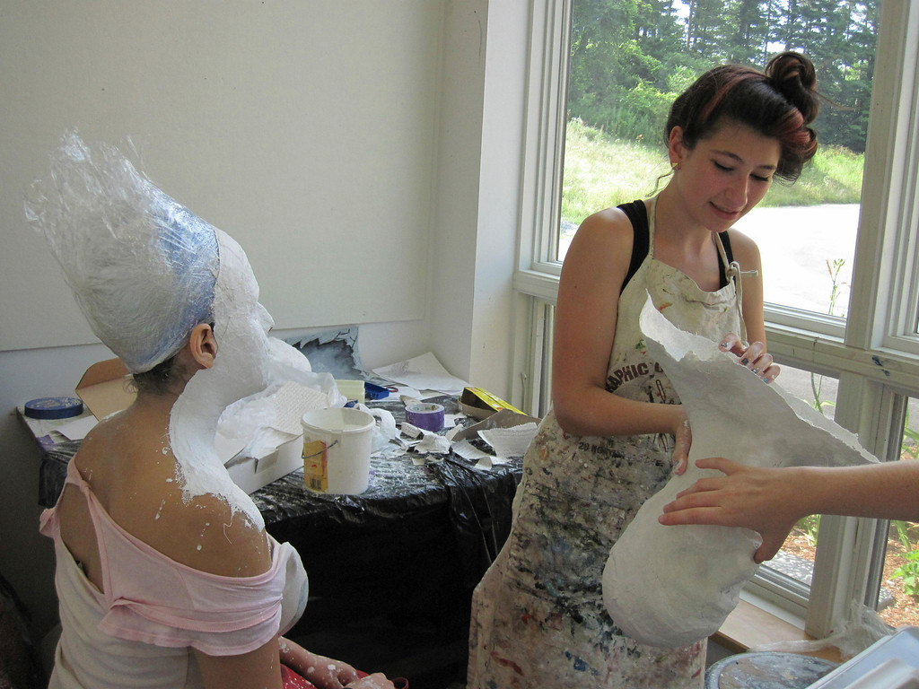 Description of . Eden Zohar (right), 15, shows a plaster cast of her head while Dania Birakh, 15, sits still as one being made of her dries. The students are participating in the summer session of Artsbridge, hosted by Buxton School in Williamstown. The program uses art and dialogue to develop constructive partnerships between Israeli, Palestinian and American youth. Sunday, July 21, 2013 Jenn Smith/Berkshire Eagle Staff