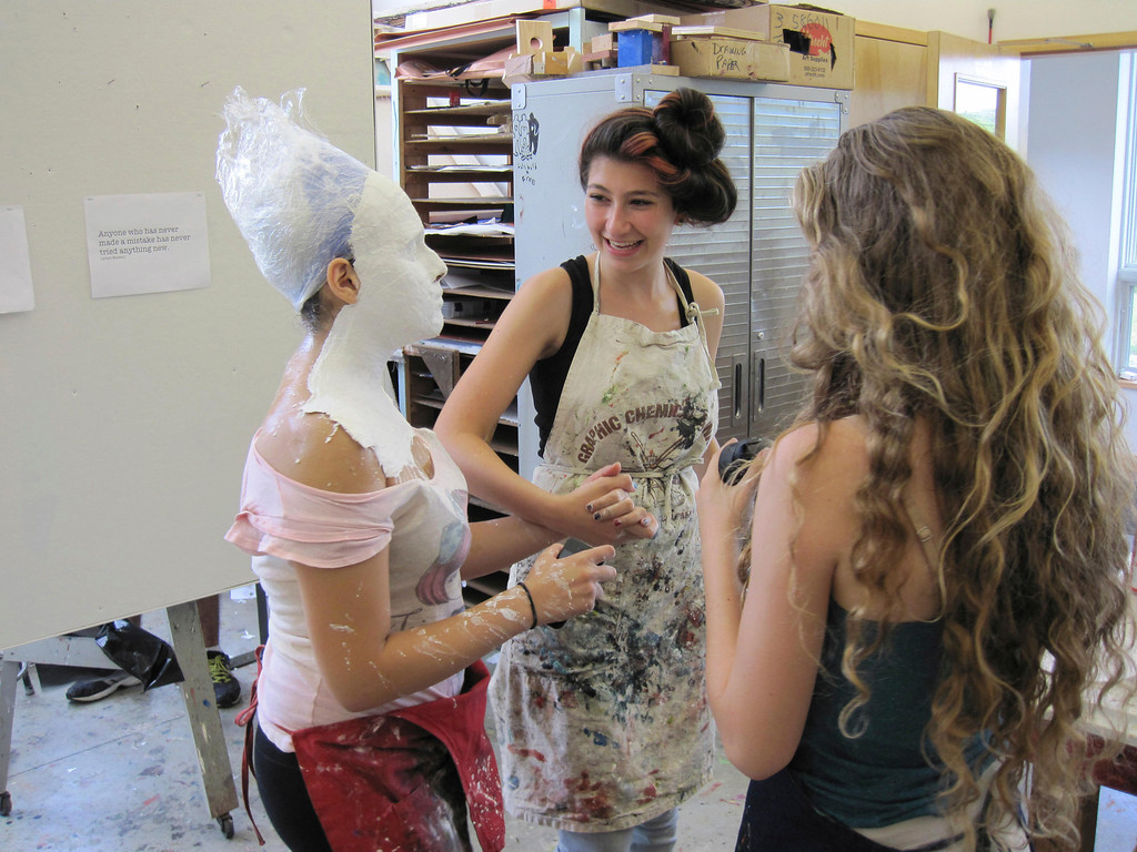 Description of . Eden Zohar leads Dania Birakh, whose head is covered in plaster, through an art studio at Buxton School in Williamstown. The students are participating in the summer session of Artsbridge, which uses art and dialogue to bring Israeli, Palestinian and American youth together. Sunday, July 21, 2013 Jenn Smith/Berkshire Eagle Staff