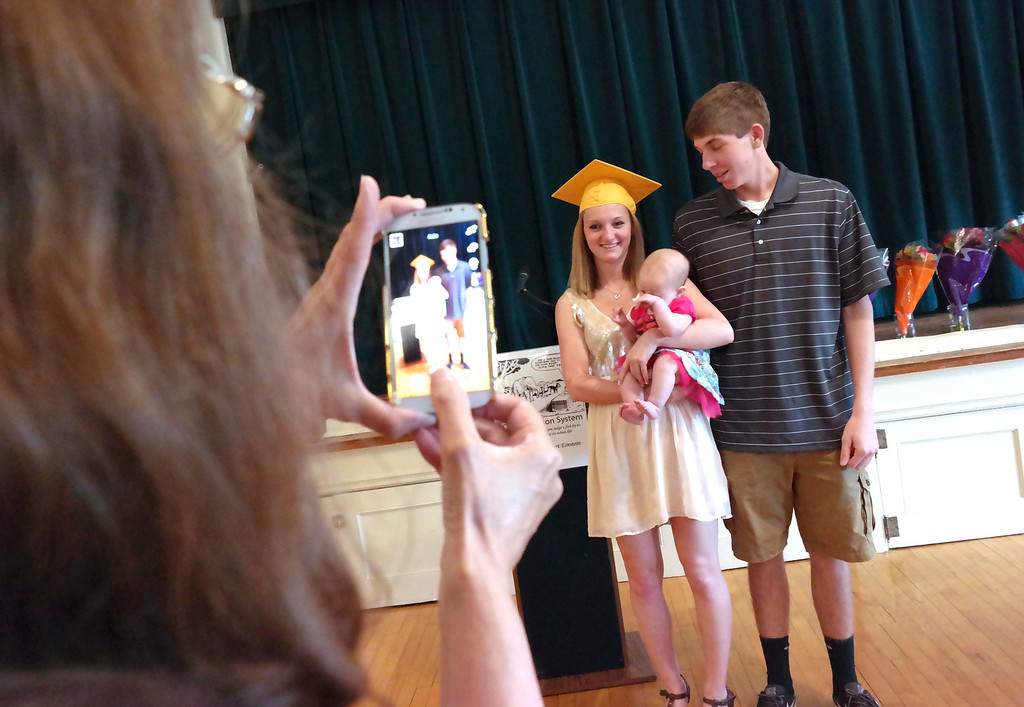Description of . Mary Tart (holding camera) takes a picture of her daughter Alexys Tart, holding her baby Emma Walton with Emma's father Brandon Walton at the Helen Berube Teen Parenting Program Commencement, Friday June 6, 2014.  Ben Garver / Berkshire Eagle Staff / photos.berkshireeagle.com