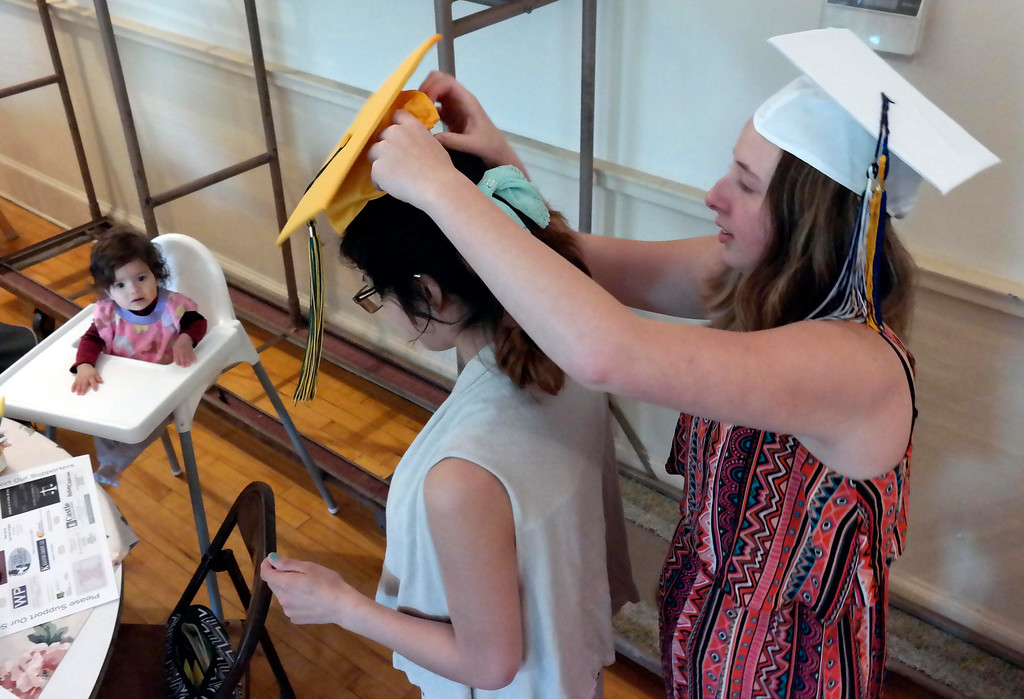 Description of . Baby hailey Van Rumund watches Krystal Ferrari put a graduation cap on her mother Ashley Reyes at the Teen Parent Program commencement in Pittsfield. Friday June 6, 2014.  Ben Garver / Berkshire Eagle Staff / photos.berkshireeagle.com