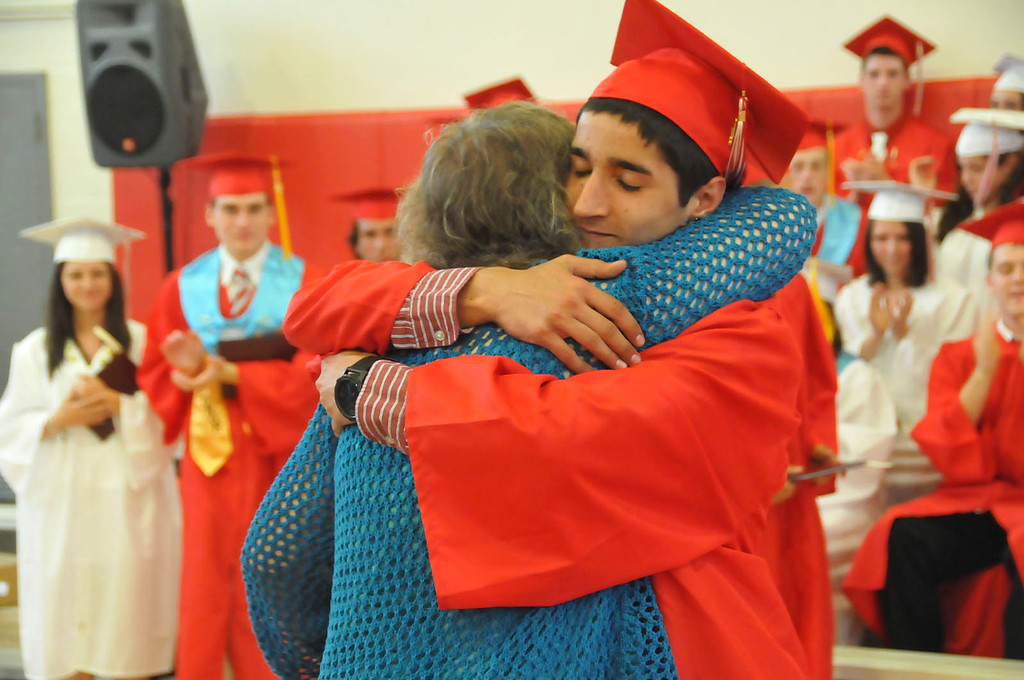 Description of . A member of the Hoosac Valley High School Class of 2014 gets a hug upon receiving his diploma during the commencement on Friday, June 6, 2014. (Scott Stafford/Berkshire Eagle Staff)