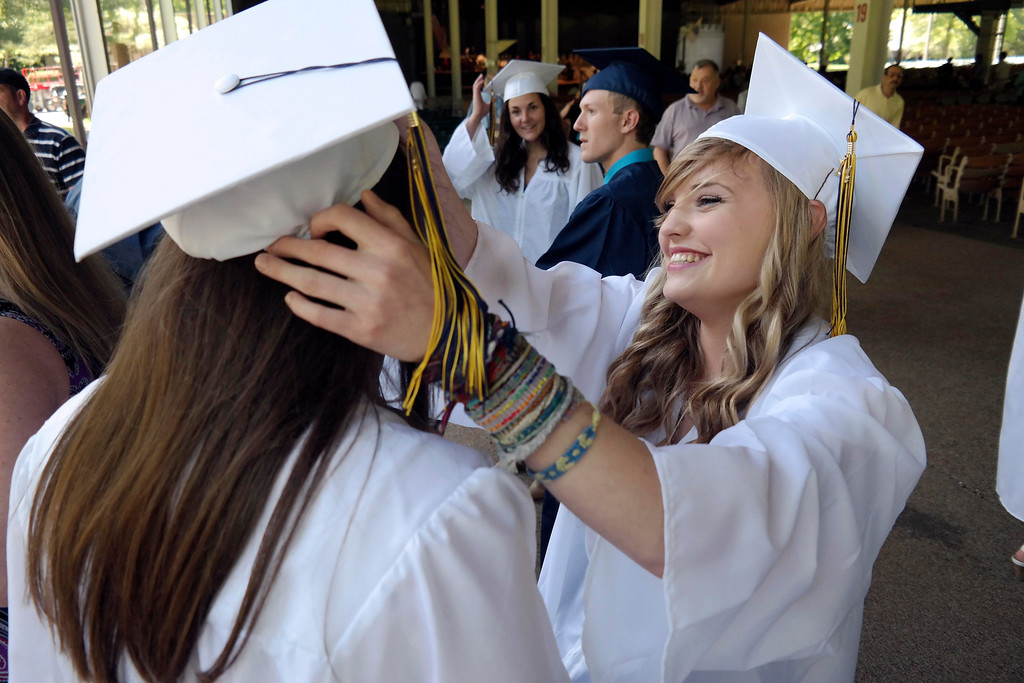 Description of . Sabrina Van Deusen helps Alicia Bazonski with her cap at the Mount Everett School graduation at Tanglewood. Saturday June 7, 2014.  Ben Garver / Berkshire Eagle Staff / photos.berkshireeagle.com