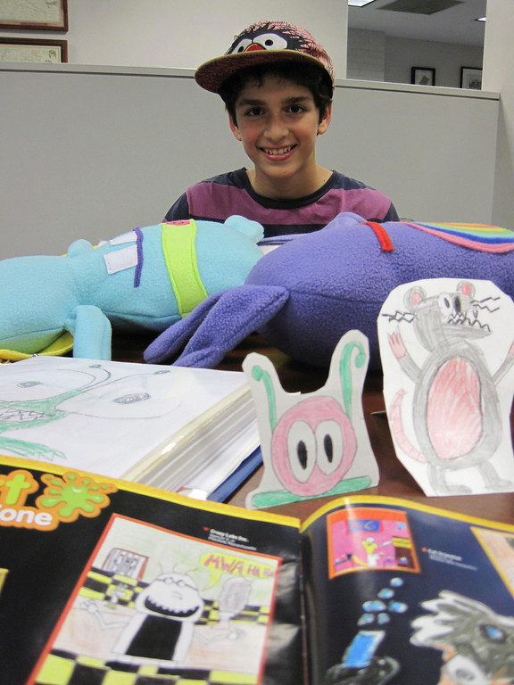 Description of . Spencer Villinski, 11, of Pittsfield, poses with his character creations, from hand drawings, paper dolls and plush monsters, as well as the drawing he has published in this month's National Geographic Kids magazine. Jenn Smith/Berkshire Eagle Staff Monday, Oct. 21, 2013