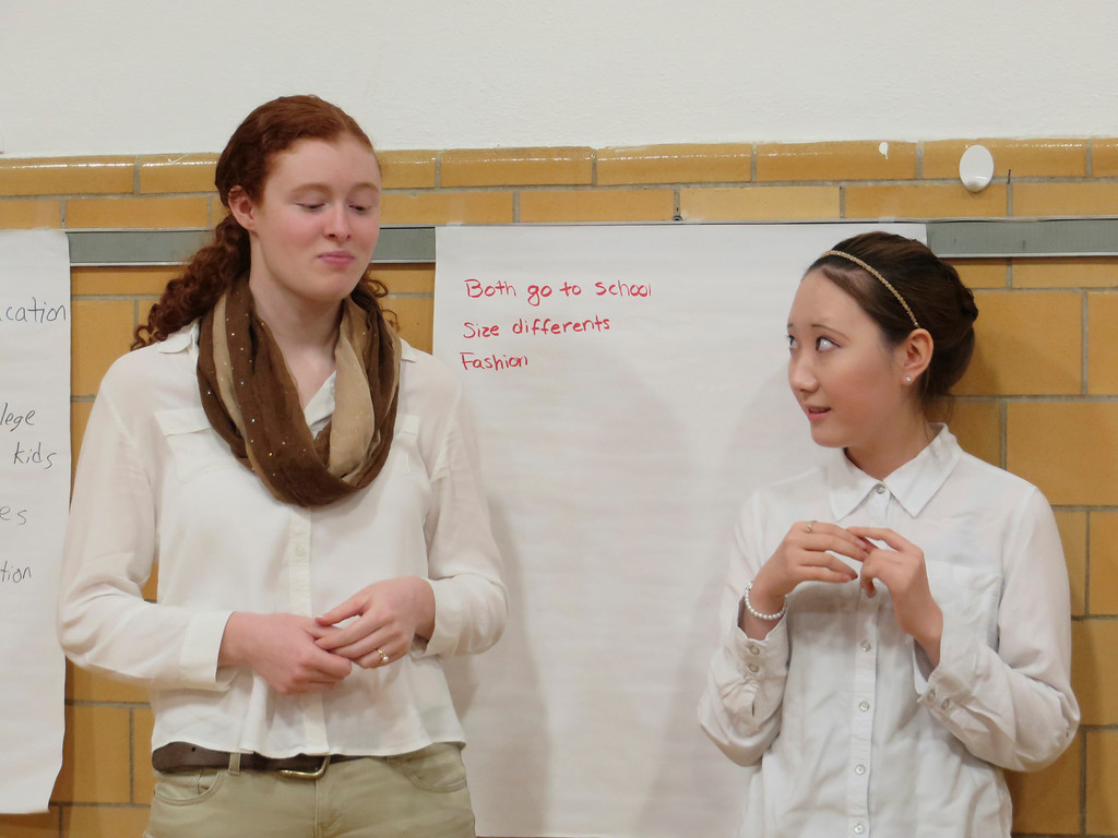 Description of . St. Joseph Central High School exchange student Jay Lee (right), 17, watches as her classmate Clarissa Mitchell, 17, tries a chocolate-covered soybean during a cultural workshop presented on North and South Korea. Jenn Smith/Berkshire Eagle Staff Friday, March 16, 2014