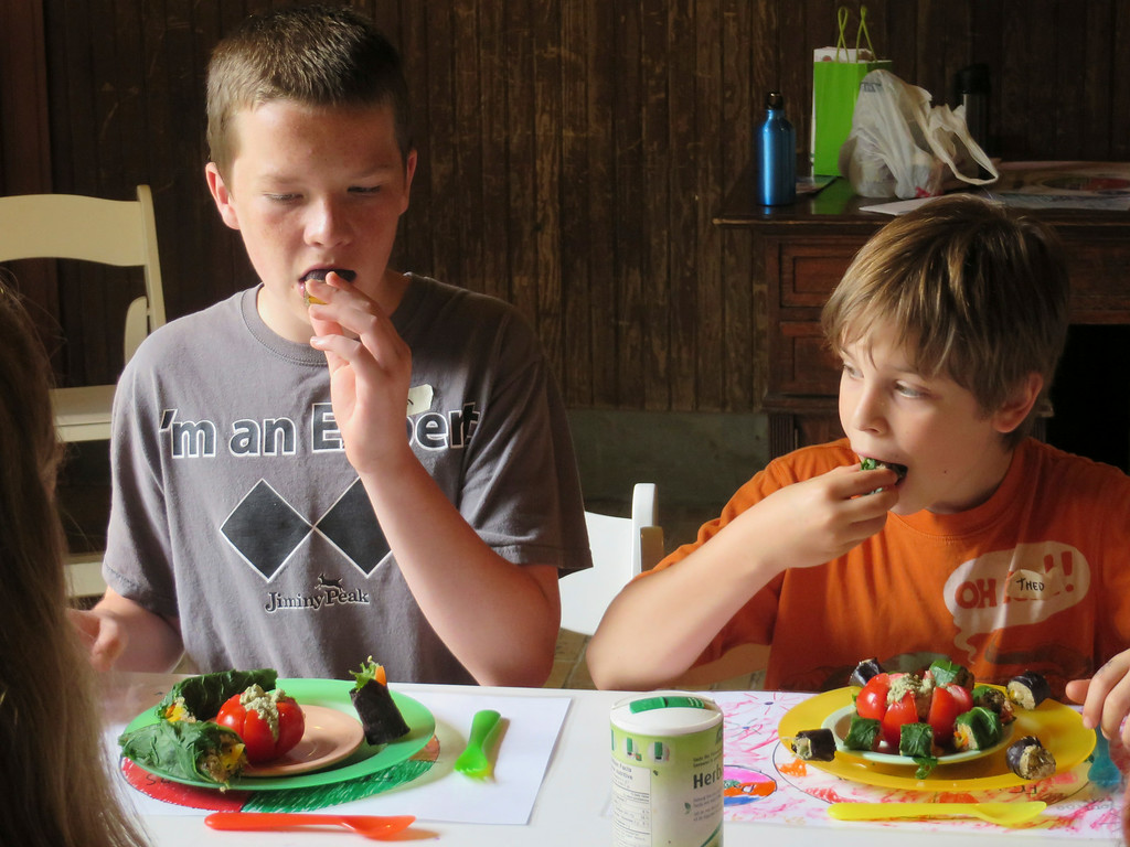 Description of . From left: Liam Nester, 13, and Theo Maurino, 10, bite into the 'sushi' rolls they made with a mix of vegetables, seeds and grains during The Nutrition Center's Food Adventures summer camp at The Mount in Lenox. Jenn Smith/Berkshire Eagle Staff/photos.berkshireeagle.com Thursday, July 3, 2014