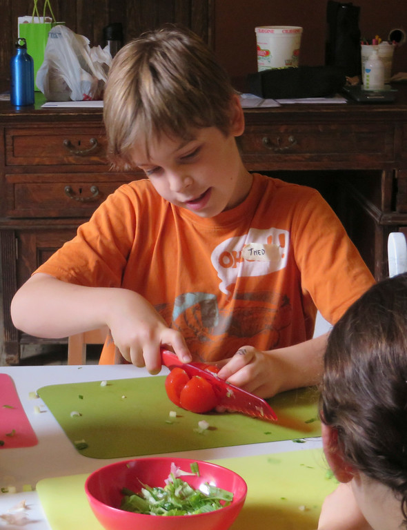 Description of . Theo Maurino, 10, of Lenox tries his hand at cutting a tomato 'blossom' during The Nutrition Center's Food Adventures summer camp held last week at The Mount in Lenox. Jenn Smith/Berkshire Eagle Staff/photos.berkshireeagle.com Thursday, July 3, 2014