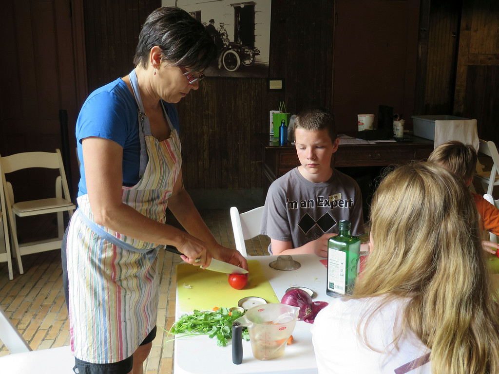 Description of . Liam Nester, 13, of Pittsfield watches as Chef Katherine Miller of Kosmic Kitchen in Lee teaches students in the Food Adventures summer camp at The Mount in Lenox how to cut tomato 'blossoms.' Jenn Smith/Berkshire Eagle Staff/photos.berkshireeagle.com Thursday, July 3, 2014