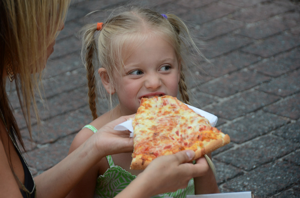 Description of . Crystal Casal holds a piece of pizza from Liberty Pizza for her daughter Londyn, 6, to eat, during Third Thursday festivities on July, 17, 2014. Gillian Jones / Berkshire Eagle Staff / photos.berkshireeagle.com