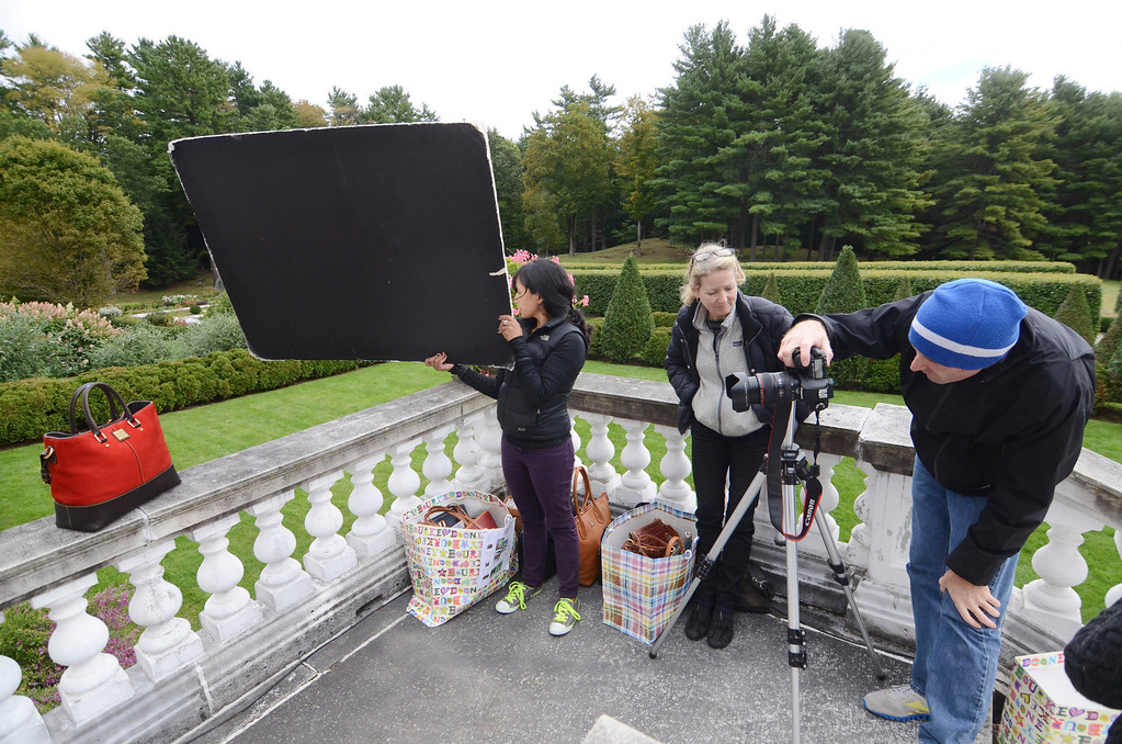 Description of . Photographer Mike Altobello, Elizabet Kane and assistant Payal Parikh photograph Dooney and Bourke handbags at the Mount, Monday September 22, 2013.  Ben Garver / Berkshire Eagle Staff