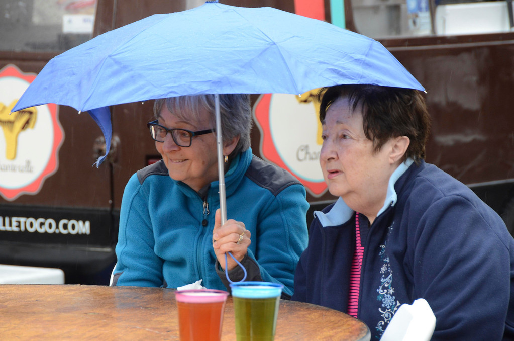 Description of . From left, Marilyn Herrman and Rosemary Casey of Pittsfield share an umbrella during the food truck community event in Palace Park to benefit Moments House in Pittsfield on Sunday, May, 4, 2014. Gillian Jones / Berkshire Eagle Staff / photos.berkshireeagle.com