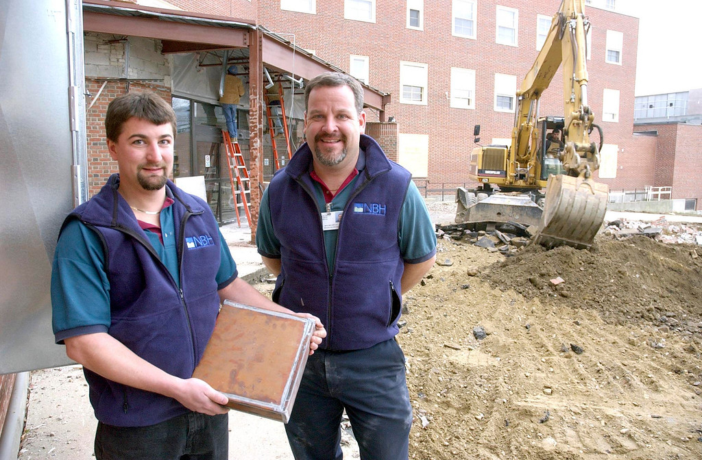 Description of . Jason rose and Don Boudreau of Northern Berkshire Health Systems found this time capsule which dates to 1953. The time capsule which measures 12x12 and is about 3 inches thick is made of copper and sealed with lead solder. It was discoved Monday near the cornerstone of the building. It is believed the time capsule was relocated to the location it was found in during the 1980's. It is under discussion as to whether or not the 51 year old artifact will be opened anytime soon. December 9, 2004 Gillian Jones/North Adams Transcript