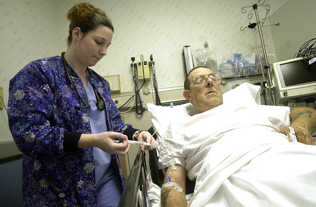 Description of . Pam Burdick, RN, gives patient Thomas Pilling a shot in his IV in the emergency room at North Adams Regional Hospital on Thursday evening.  Thu Nov 18 2004. Phot by Caroline Bonnivier Snyder