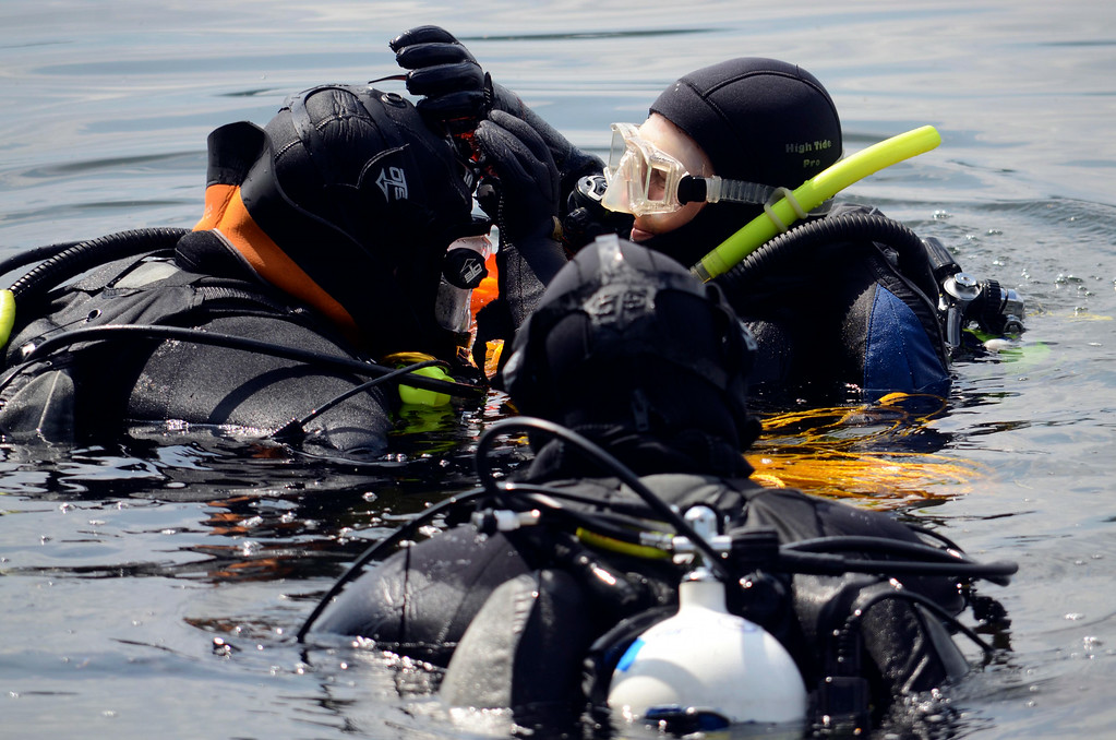 Description of . Members of the Berkshire County Sheriff department dive team prepare to search for a discarded handgun in Onota Lake, Wednesday Aug 20, 2014.  Pictured are Superintendant Jack Quinn (left), Laurie Rock (right) and Lt. Col. Tom Grady (front).  The handgun in question was thrown in the lake after a man decided not to use it to take his own life three years ago. Ben Garver / Berkshire Eagle Staff / photos.berkshireeagle.com