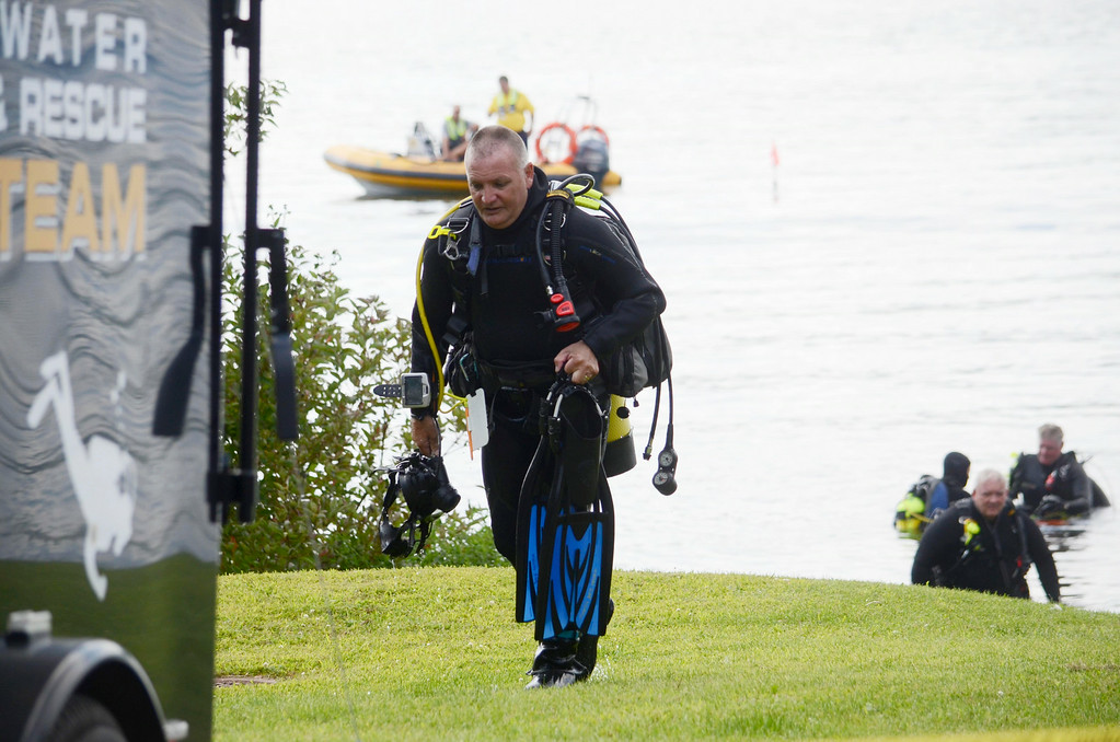 Description of . Diver Jim Rathbun breaks to get a fresh tank ot air while searching at Onota Lake for a discarded handgun, Wednesday Aug 20, 2014. The handgun in question was thrown in the lake after a man decided not to use it to take his own life three years ago. Ben Garver / Berkshire Eagle Staff / photos.berkshireeagle.com