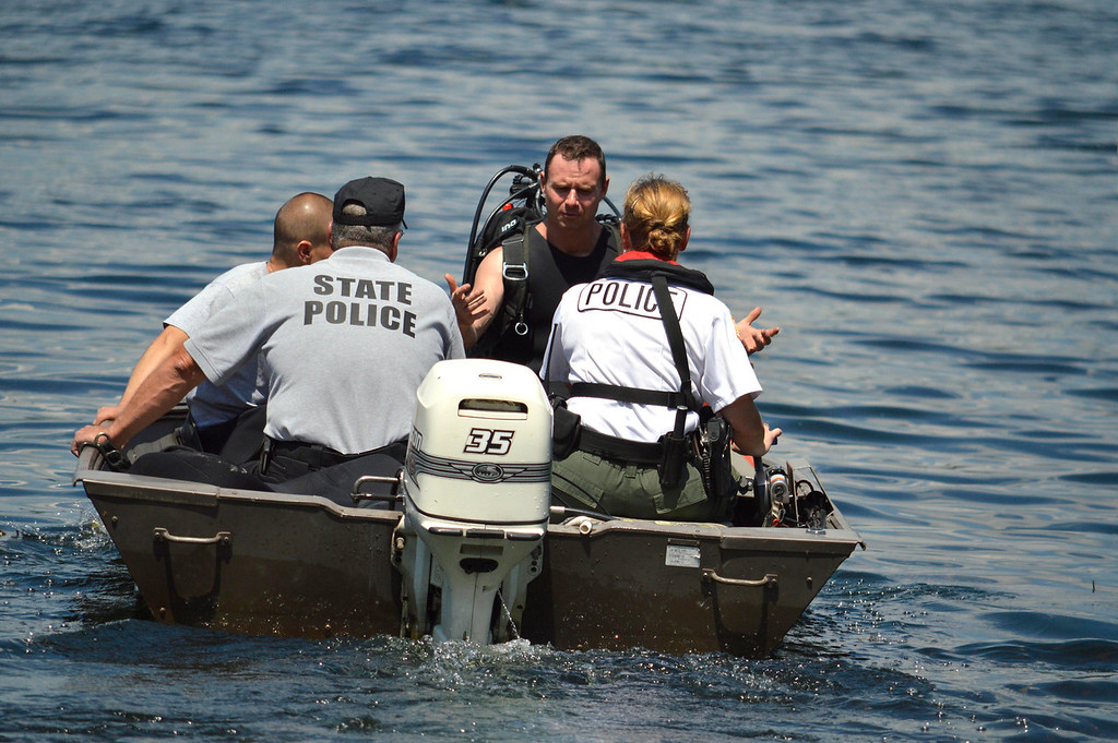 Description of . A diver gestures during a search of Greenwater Pond in Becket for clues related to the abduction of James Lusher, Tuesday July 16, 2013. Ben Garver / Berkshire Eagle Staff