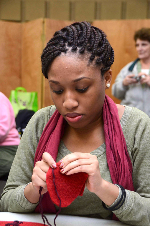 Description of . MCLA sophomore Sherley Jules, sews mittens for children in the North Adams Public Schools and Northern Berkshire Headstart, during the 2014 MLK Jr. 'Day of Service' at the MCLA Church Street Center on Monday, Jan. 20, 2014.  (Gillian Jones/Berkshire Eagle Staff)