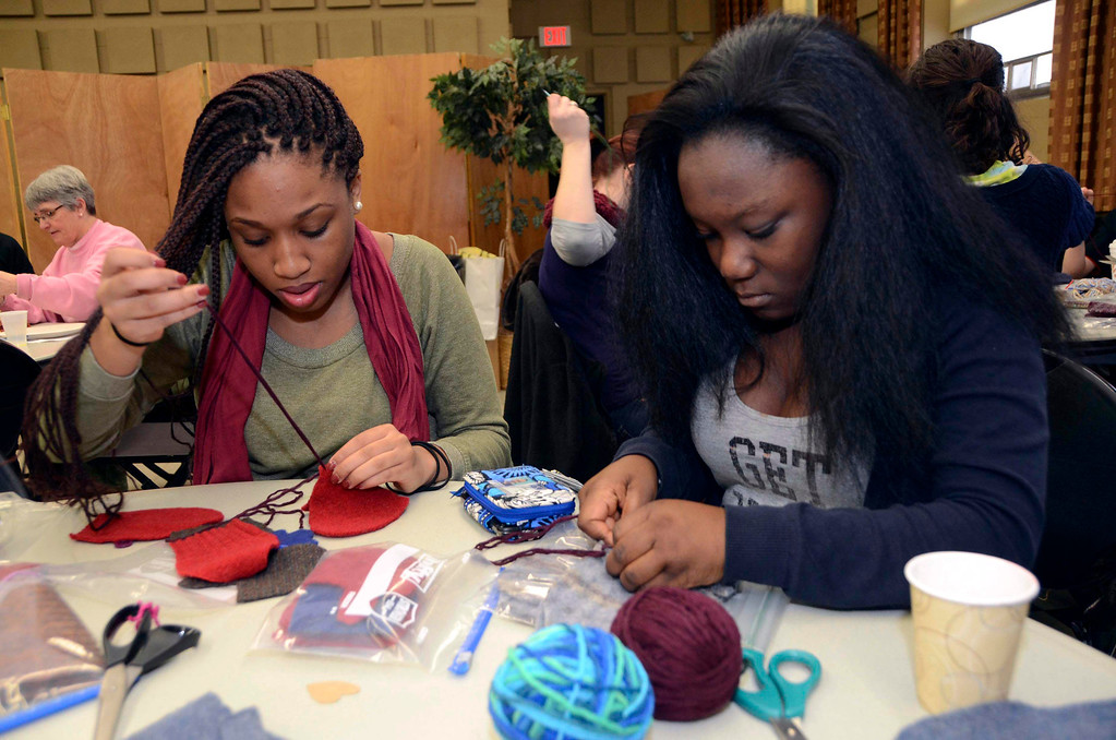 Description of . MCLA sophomores Sherley Jules and Kenya Joseph sew mittens for children in the North Adams Public Schools and Northern Berkshire Headstart, during the 2014 MLK Jr. 'Day of Service' at the MCLA Church Street Center on Monday, Jan. 20, 2014.  (Gillian Jones/Berkshire Eagle Staff)