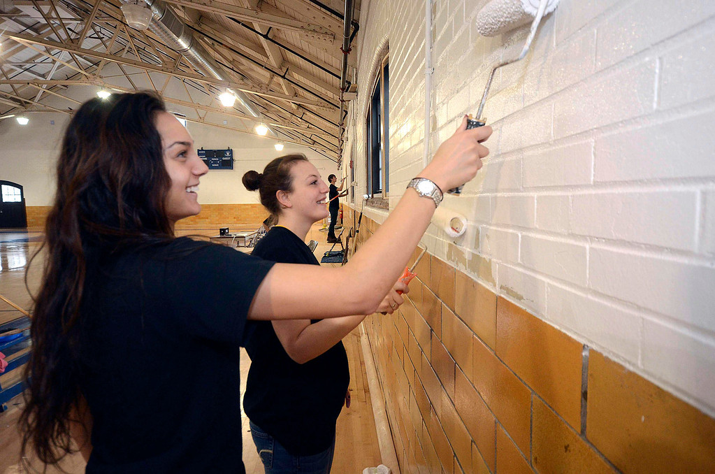 Description of . Rachel Mills and Amanda Fleming, members of the MCLA womens' volleyball team, paint the walls of the North Adams Armory during the 2014 MLK Jr. 'Day of Service' on Monday, Jan. 20, 2014.(Gillian Jones/Berkshire Eagle Staff)