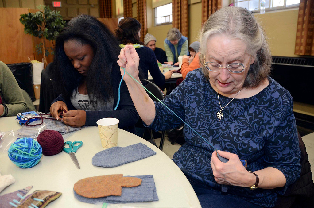 Description of . MCLA sophomore Kenya Joseph and Katherine Montgomery, of North Adams, sew mittens for children in the North Adams Public Schools and Northern Berkshire Headstart, during the 2014 MLK Jr. 'Day of Service' at the MCLA Church Street Center on Monday, Jan. 20, 2014.  (Gillian Jones/Berkshire Eagle Staff)