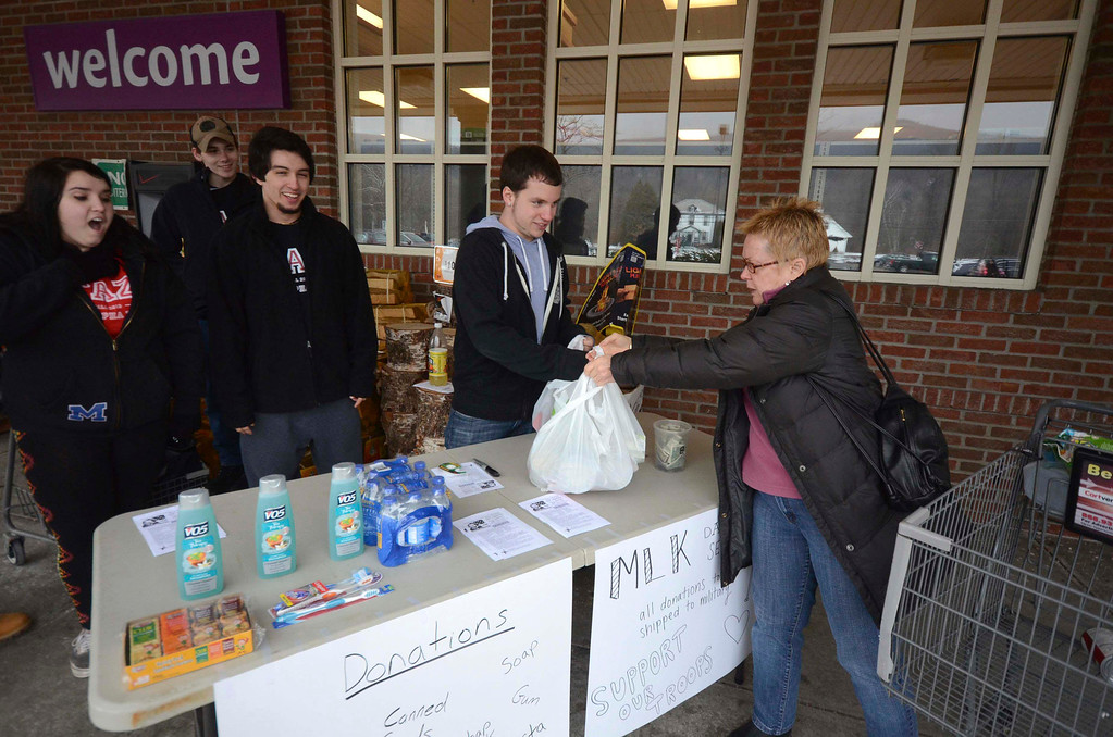Description of . Debbie Haig, of New Ashford, drops off a donation with volunteer Justin Balsamo during the 2014 MLK Jr. 'Day of Service' on Monday, Jan. 20, 2014. MCLA students in the Tau Alpha Zeta co-ed fraternity took donations of food, toiletries and other items, which will be used in military care packages, from customers of Stop and Shop in North Adams. (Gillian Jones/Berkshire Eagle Staff)