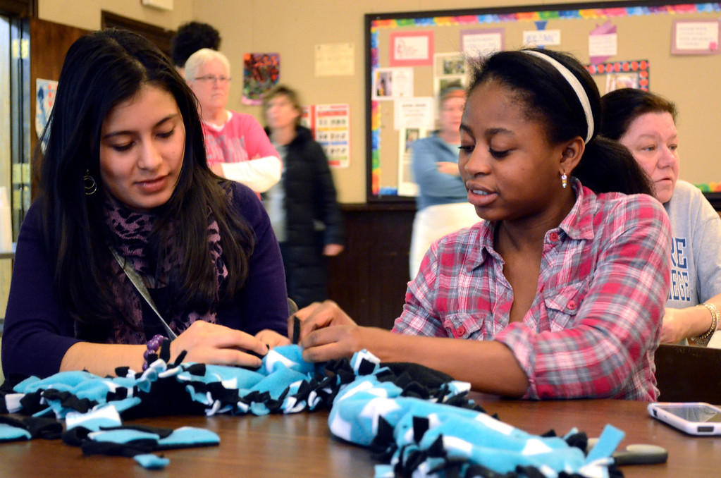 Description of . BCC students Kimberly Figueroa and Esperance Behanzin make scarves at the First United Methodist Church as part of a Martin Luther King Jr. 'Day of Service.'  The scarves were given away at a lunch held in honor of Dr. King at the church.on Monday, Jan. 20, 2014.  (Ben Garver / Berkshire Eagle Staff)