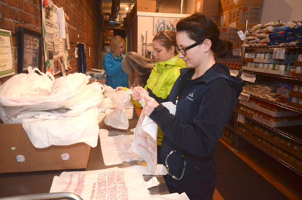 Description of . MCLA sophomores Emily O'Toole and Alexandra Kadell open plastic bags to hold food at The Friendship Center Food Pantry on Eagle Street in North Adams, during the 2014 MLK Jr. 'Day of Service' on Monday, Jan. 20, 2014. (Gillian Jones/Berkshire Eagle Staff)