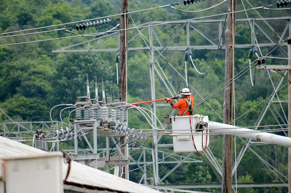 Description of . A National Grid worker works at the Adams substation as crews work to restore power to North Berkshire County. Tuesday July 8, 2014.  Ben Garver / Berkshire Eagle Staff / photos.berkshireeagle.com