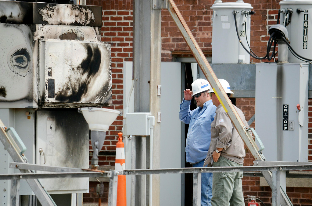 Description of . Nationa Grid worker examine a switch that caught fire in the Adams substation, resulting in widespread power outages in North Berkshire County.  Tuesday July 8, 2014.  Ben Garver / Berkshire Eagle Staff / photos.berkshireeagle.com