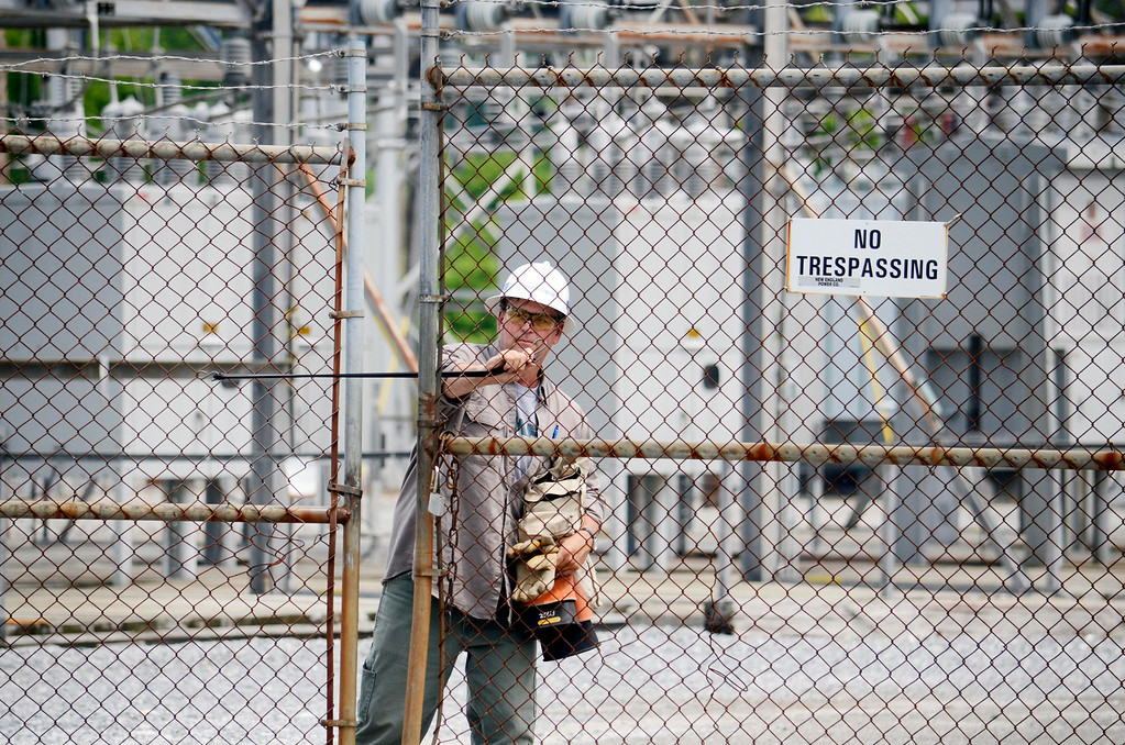 Description of . A National Grid worker closes the gate behind him as he approached the Adams substation. Tuesday July 8, 2014.  Ben Garver / Berkshire Eagle Staff / photos.berkshireeagle.com