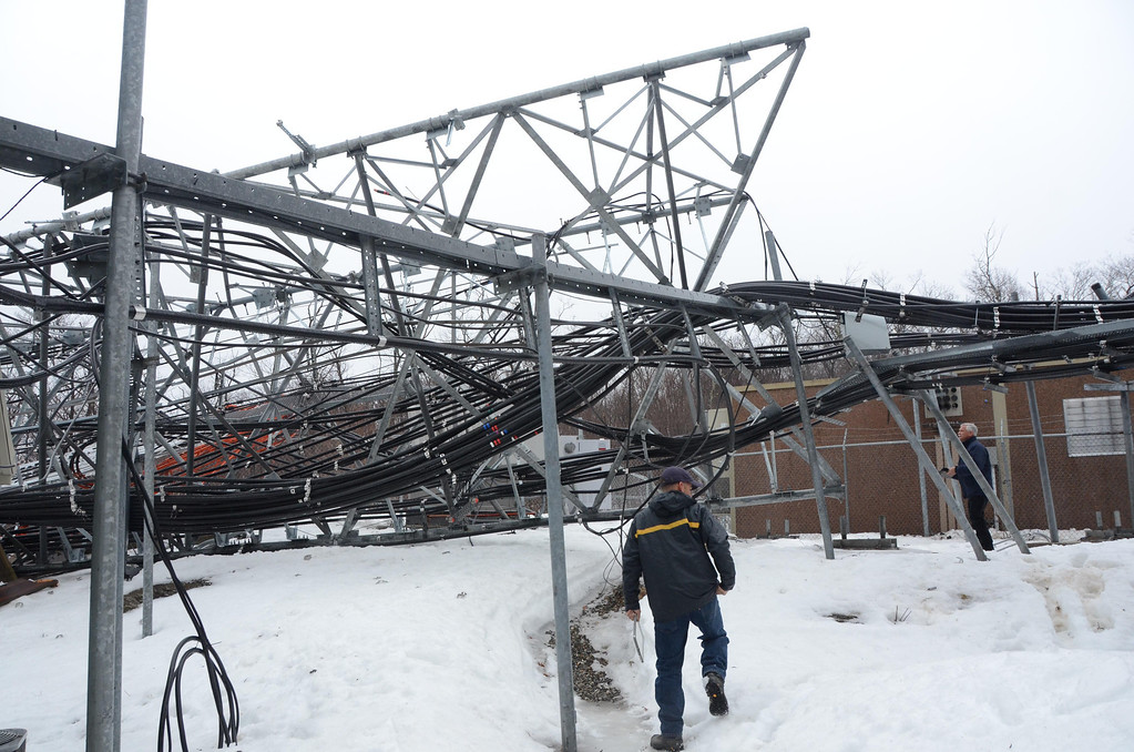 Description of . High winds overnight have toppled the communications tower on Florida Mountain at the Western Summit in North Adams impacting cell service to North Adams and some surrounding communities. Workers with Pittsfield Communications inspect the damage. Gillian Jones / Berkshire Eagle Staff / photos.berkshireeagle.com
