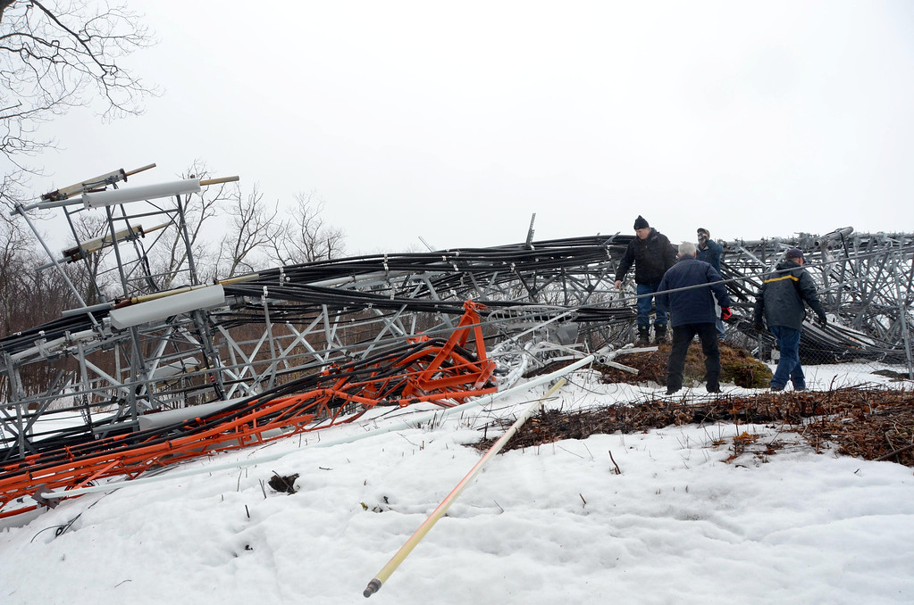 Description of . High winds overnight have toppled the communications tower on Florida Mountain at the Western Summit in North Adams impacting cell service to North Adams and some surrounding communities. Workers with Pittsfield Communications access the damage. Gillian Jones / Berkshire Eagle Staff / photos.berkshireeagle.com