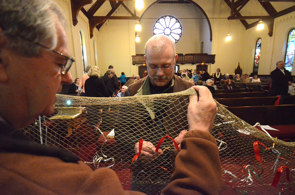 Description of . North Adams Fire Director Steve Meranti ties a ribbon to a net with other members of the community and NARH former employees as they gather at the First Congregational Church in North Adams on Sunday, March, 30, 2014 for a vigil. People were asked to tie a ribbon, representing their worries, on a net as a symbolic gesture of casting one's worries away. Gillian Jones / Berkshire Eagle Staff / photos.berkshireeagle.com