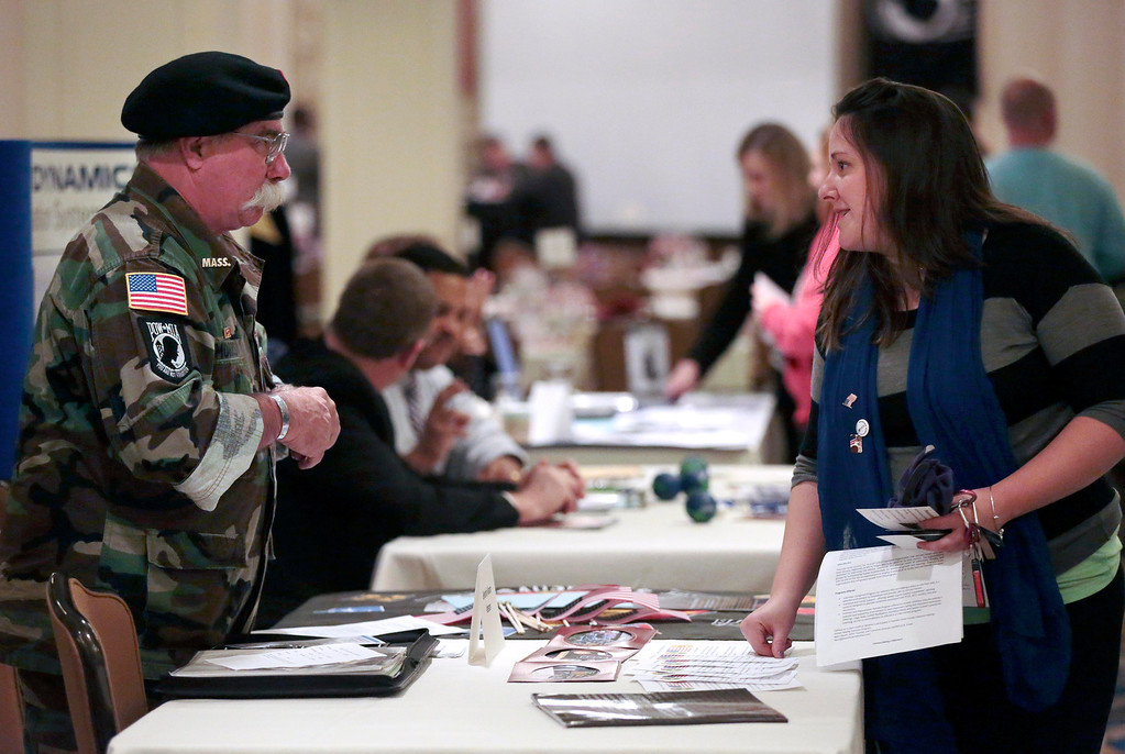 Description of . Veterans Henry Morris and Lisa Catullo chat at the Vietnam Veterans Berkshire Chapter 65 table at the Veteran's Expo at the Crowne Plaza hotel in Pittsfield. Friday, November 15, 2013. (Stephanie Zollshan | Berkshire Eagle Staff)