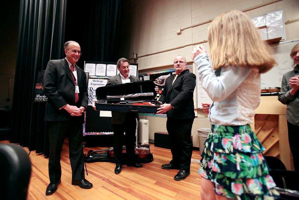 Description of . Karissa Yzerman-Gleason walks up to accept her violin from Mayor Daniel Bianchi, left, Domenic Izzi, center, and Mike Fillipi, as one of six Herberg Middle School students to receive musical instruments from the Domenic A. Izzi Jr. Foundation for Young Aspiring Musicians. Thursday, April 3, 2014. Stephanie Zollshan / Berkshire Eagle Staff / photos.berkshireeagle.com