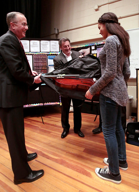 Description of . Kamea Quetti accepts her violin from Mayor Daniel Bianchi, left, and Domenic Izzi as one of six Herberg Middle School students to receive musical instruments from the Domenic A. Izzi Jr. Foundation for Young Aspiring Musicians. Thursday, April 3, 2014. Stephanie Zollshan / Berkshire Eagle Staff / photos.berkshireeagle.com