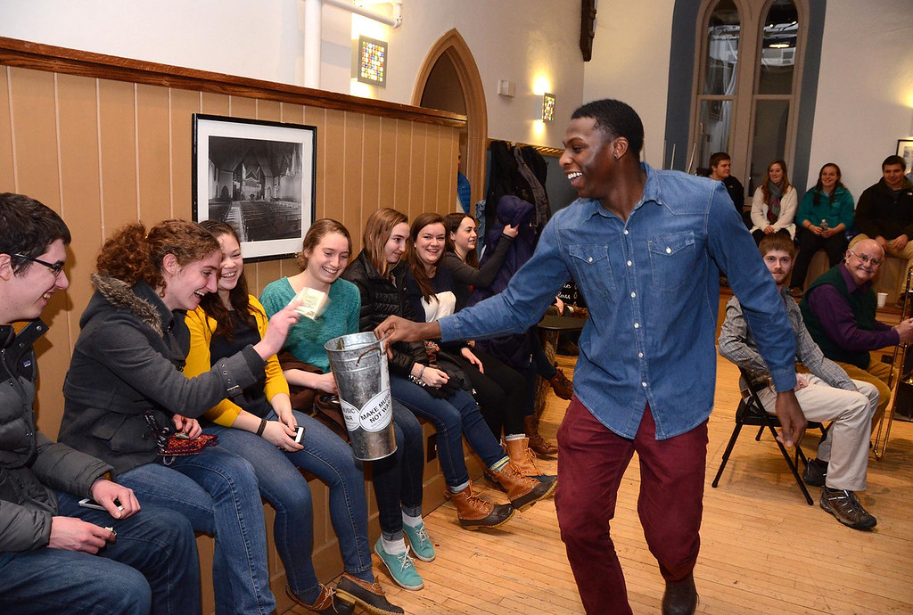 Description of . Wiliams College students in Andy Kelly's music class performed in Goodrich Hall on Monday, January, 27, 2014, to raise money to help buy musical instruments for students at Crosby Elementary School in Pittsfield. Williams College senior Demarius Edwards dances as he carries a bucket through the audience to collect donations.  Gillian Jones/Berkshire Eagle Staff
