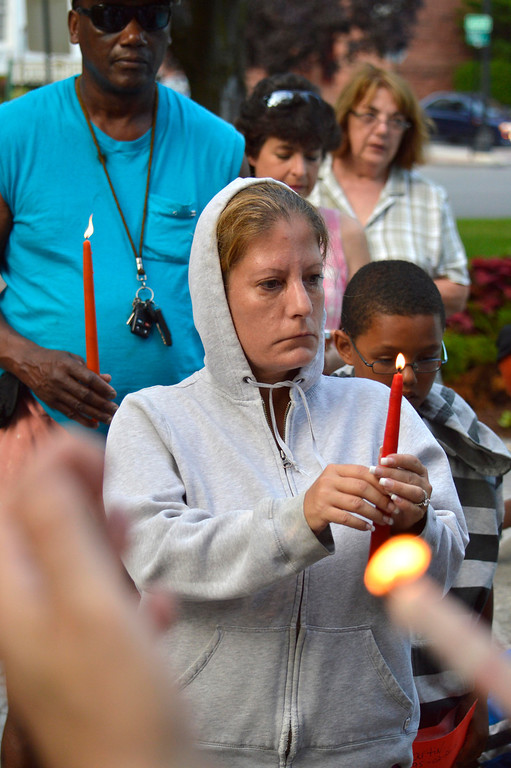 Description of . Lisa Clayton holds a candle to honoto Trayvon Martin. At 7:17pm protesters lit candles in a vigil for Trayvon Martin in Park Square in Pittsfield, Wednesday July 17, 2013. Ben Garver / Berkshire Eagle Staff